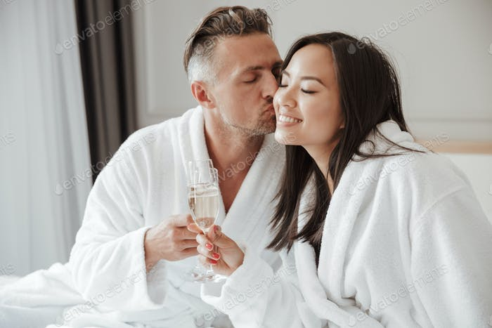Image of caucasian handsome man kissing beautiful asian woman on