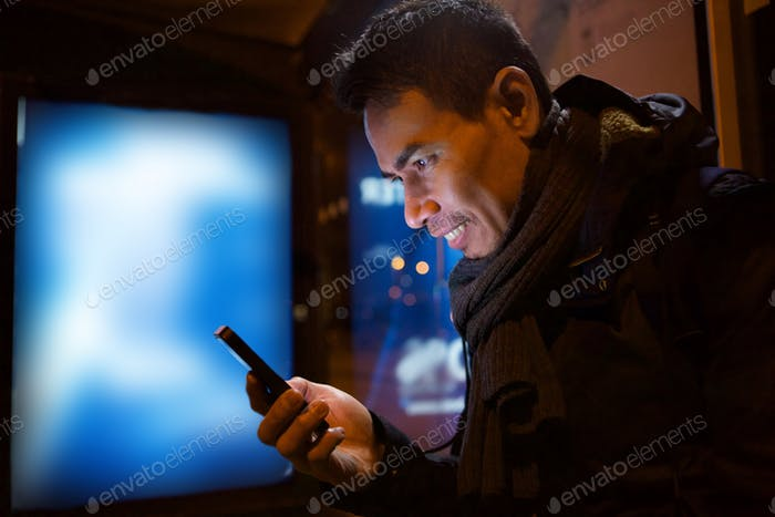 Older asian man with smartphone at night in city