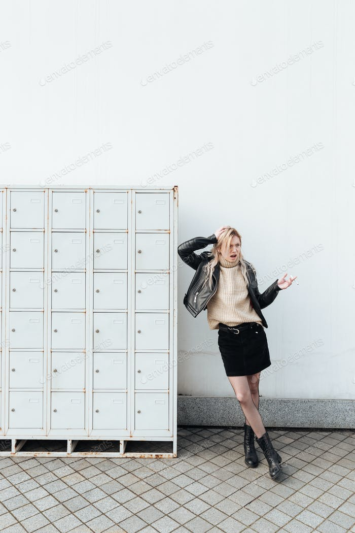 Angry young blonde lady standing near safes