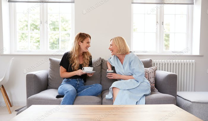 Senior Mother With Adult Daughter Sitting On Sofa Indoors Drinking Coffee And Talking