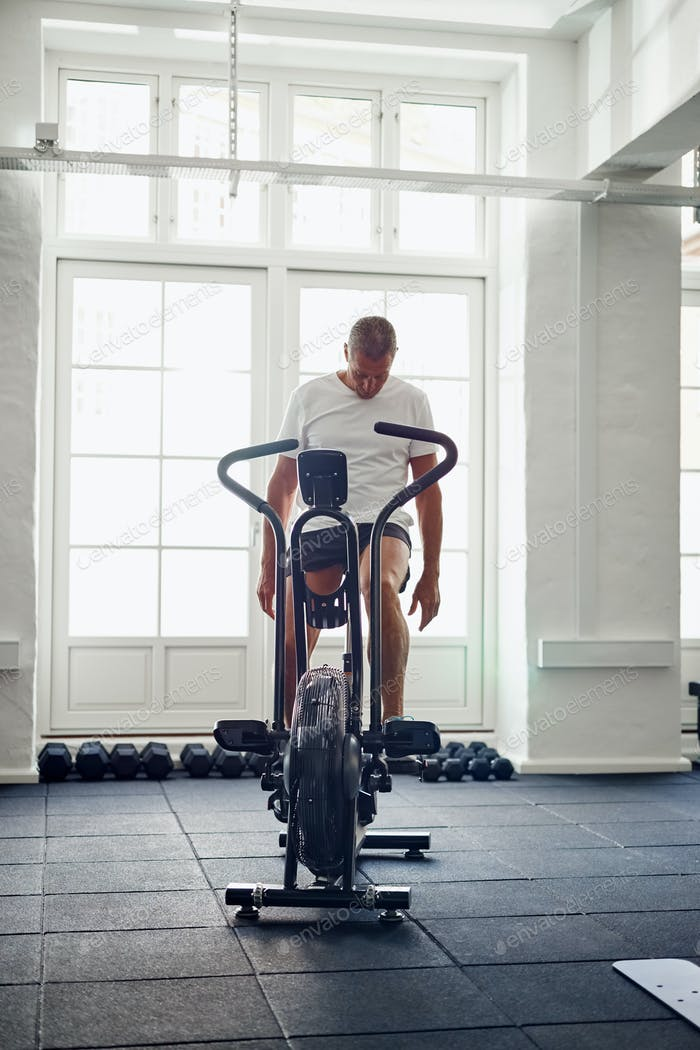 Mature man in sportswear cycling alone in a gym