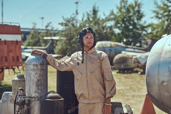 Mechanic in uniform near to combat bombs for a bomber aircraft in an open-air museum.