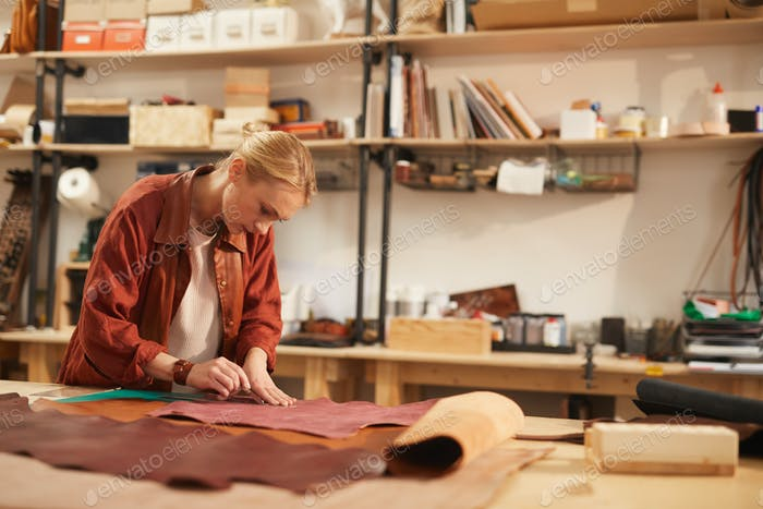 Blond Woman Cutting Out Leather