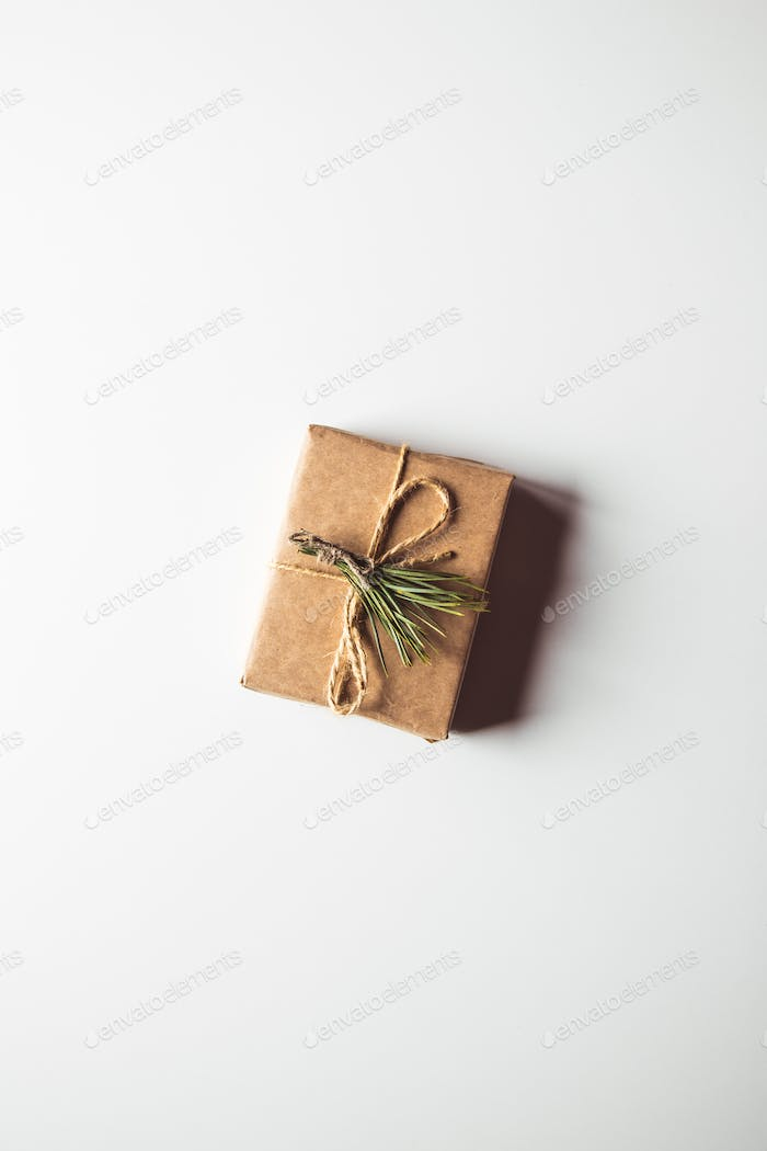 Gift box wrapped in brown recycled paper and tied sack rope top view isolated on white background
