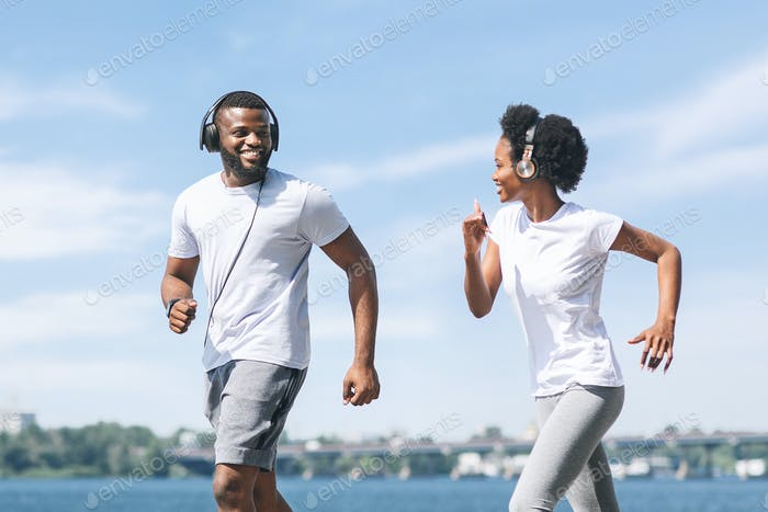 Black Couple Trotting And Jogging Along River Bank