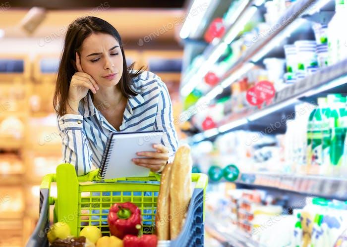 Junge Frau mit Einkaufsliste im Supermarkt