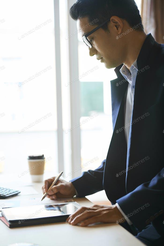 Geschäftsmann überprüfen Dokument auf Tablet-Computer
