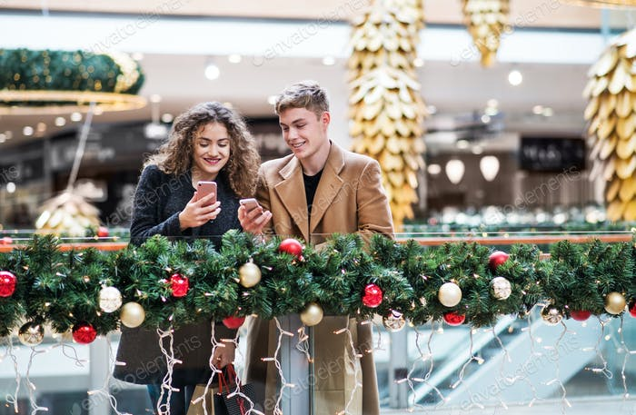 A young couple with smartphone in shopping center at Christmas.