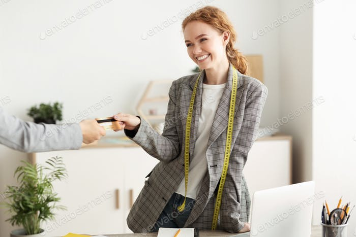 Happy red-haired female tailor taking credit card