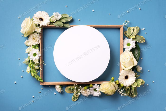 White roses, lily, gerbera and circle shape paper over blue background. Flat lay, top view. Creative