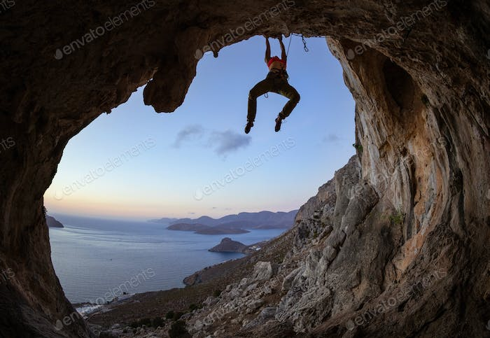 Young woman climbing in cave at sunset
