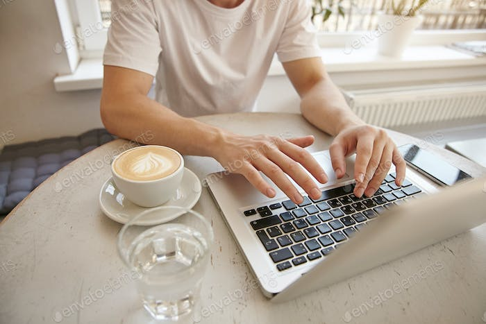 Closeup indoor photo of young guy with hands on the keyboard, working remotely with laptop