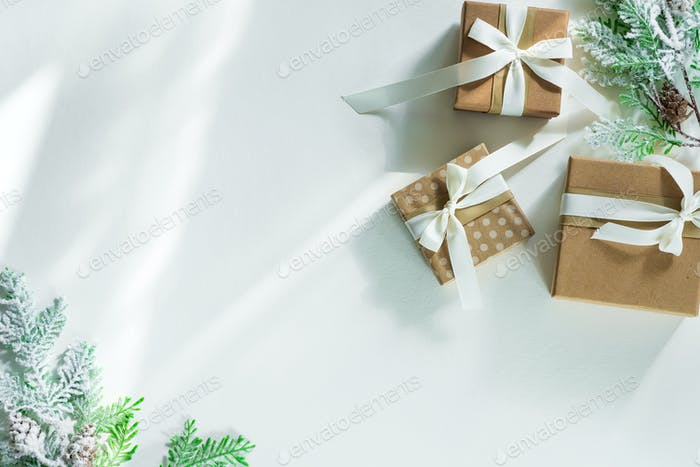 Gift boxes with snow fir branches and sunlight rays on a white background. Christmas card. Flat lay