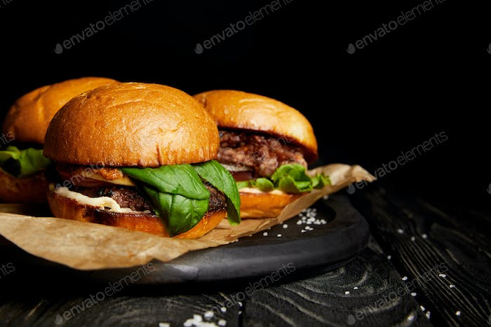 Set of junk food with hot delicious burgers on wooden board