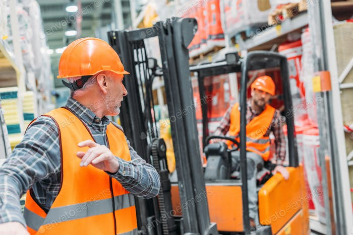 male worker and his colleague working with forklift machine in storehouse