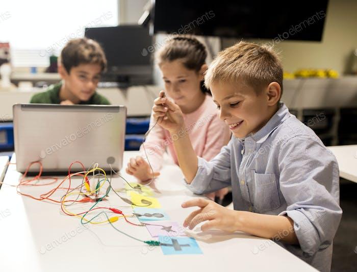 Kinder, Laptop und Erfindungsset an der Roboterschule