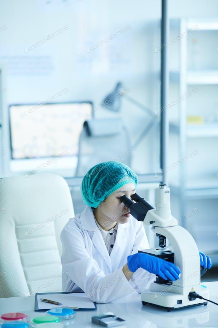 Woman analyzing with microscope
