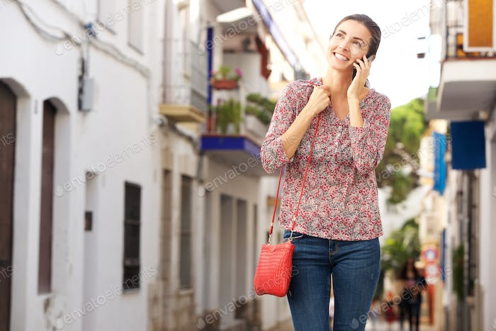 Attractive woman walking outdoors on street and using mobile phone