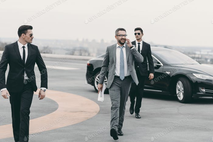 businessman walking with bodyguards on helipad and talking by smartphone