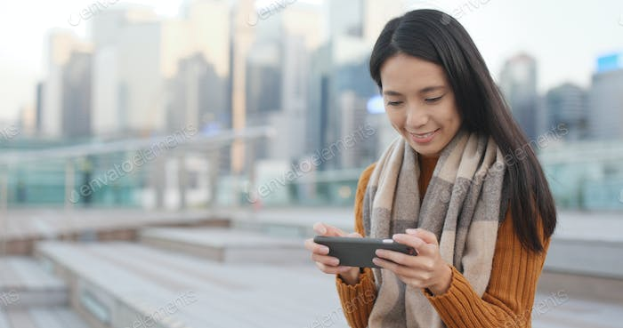 Woman playing game on smart phone in city