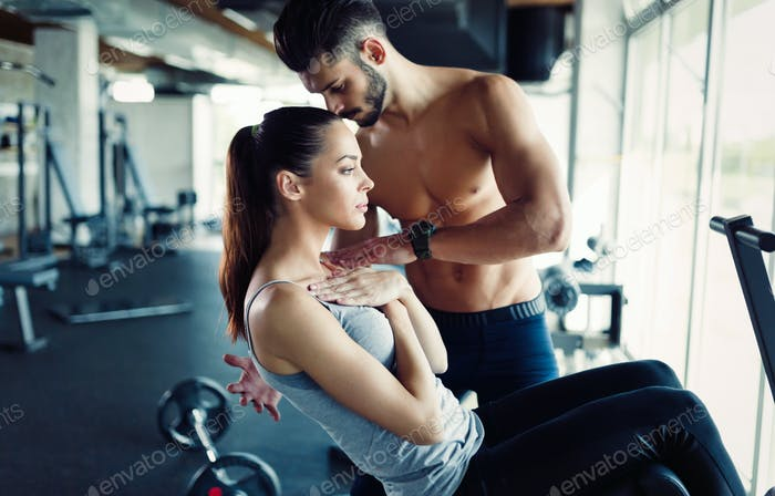 Young woman doing exercises for abs with personal trainer