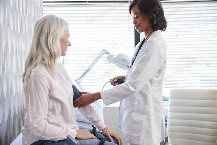 Frau Patienten mit Blutdruck von weiblichen Arzt in Büro genommen