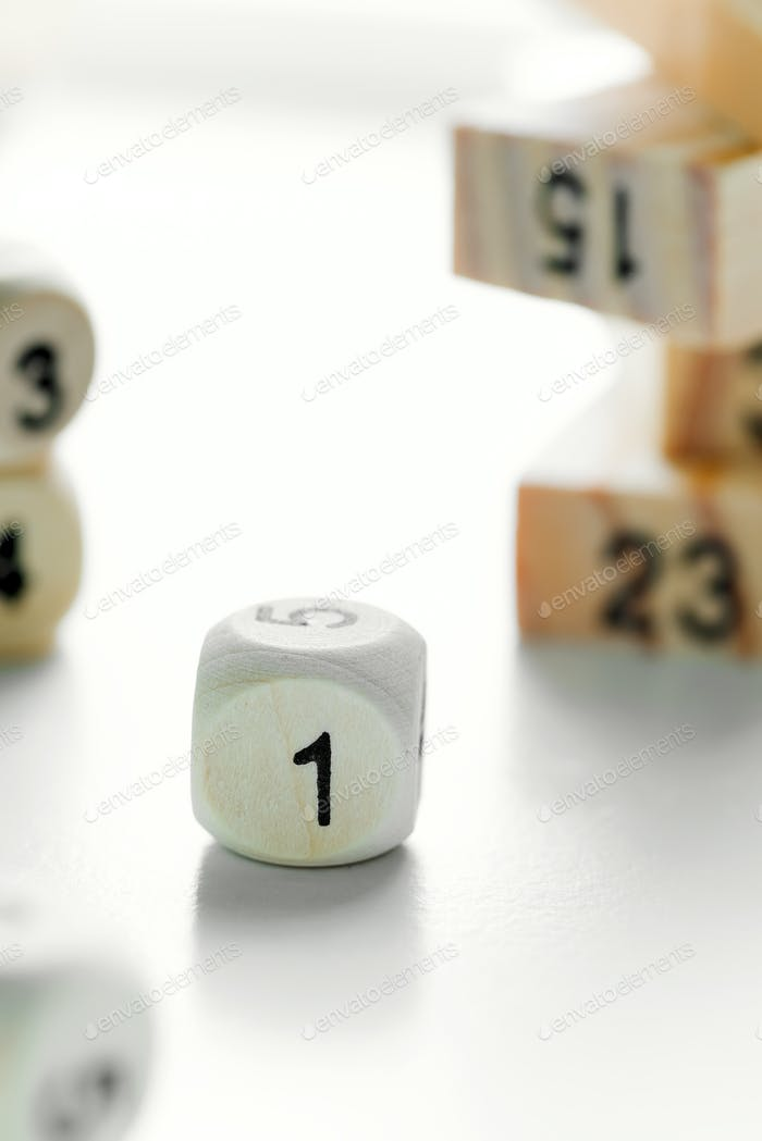 Number one on the face of wooden dice cube on a light grey background with blurred piramyd from