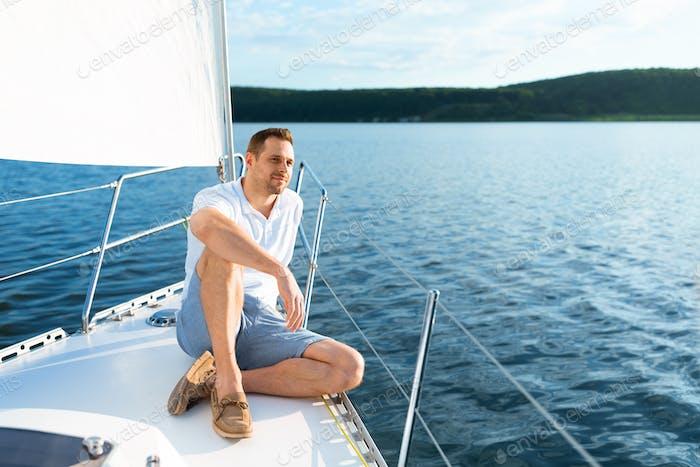 Happy Man Sitting On Yacht Deck Enjoying Sea Ride