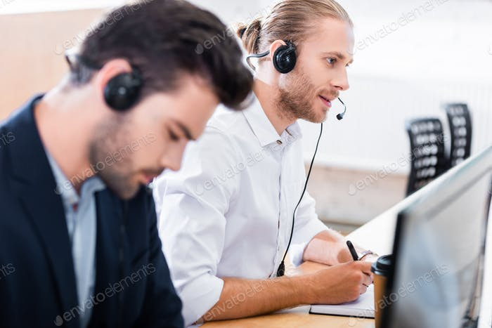 selective focus of male call center operators in headsets at workplace in office