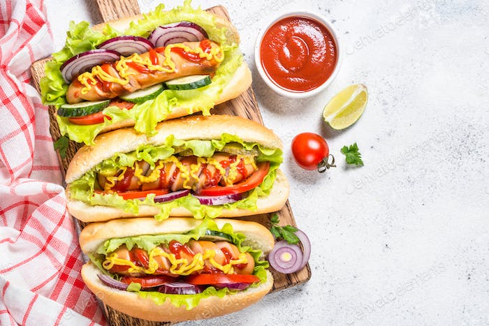 Hot dog with fresh vegetables on white top view.