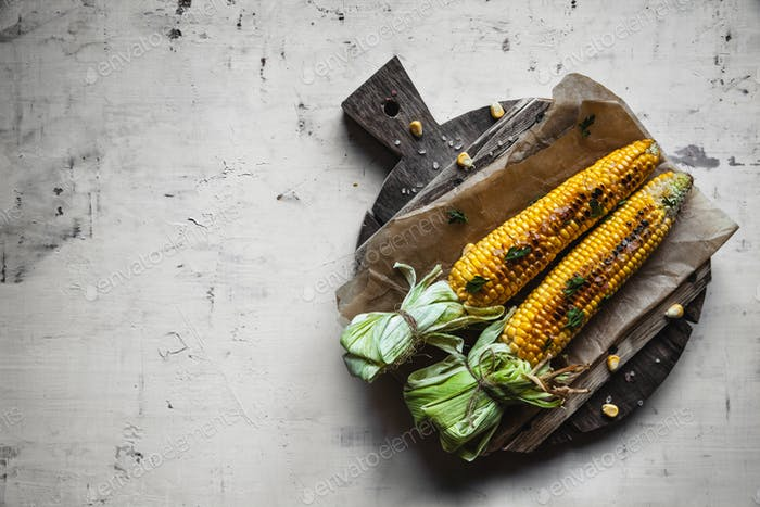 Grilled corn cobs with sauce, coriande on old shabby wooden white background. Mexican food. Top view