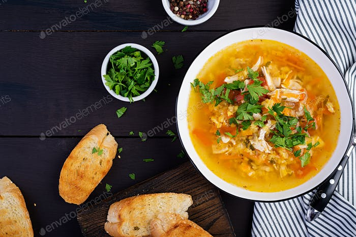 Rote Linsensuppe mit Hühnerfleisch und Gemüse Nahaufnahme auf dem Tisch. Gesundes Essen. Ansicht von oben