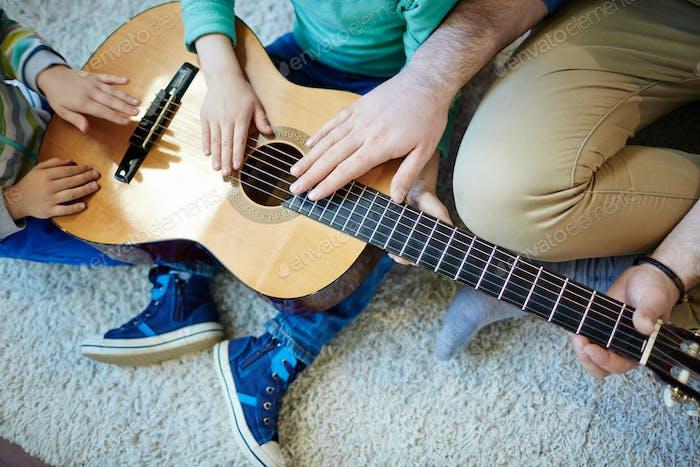 Touching strings of guitar