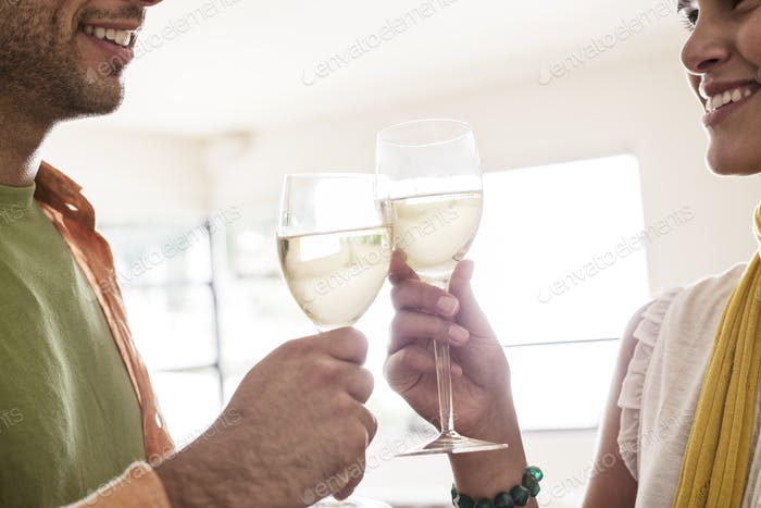 Hispanic couple having a glass of white wine together.