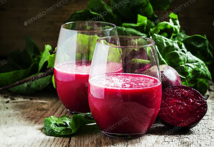 Beetroot smoothie in a large glass, fresh beets with tops