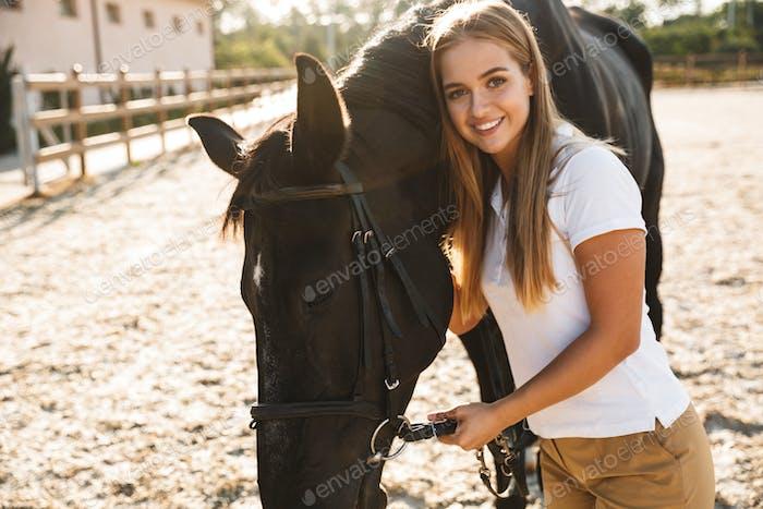 Schöne Frau mit Pferd auf dem Land
