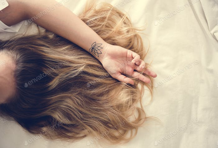 Woman with brunette hair lying down on the bed