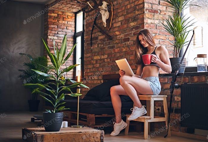 Atractiva mujer deportiva usando Tablet PC en la habitación interior loft.