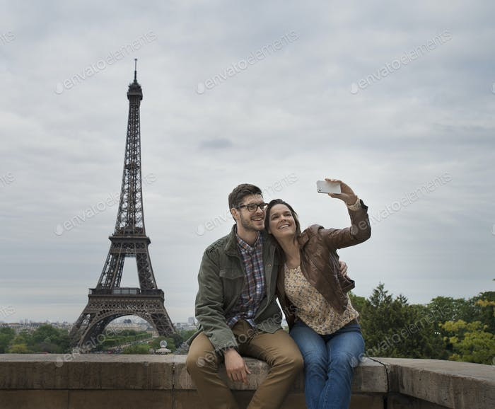 A couple seated side by side taking a selfy with the Eiffel Tower in the background.
