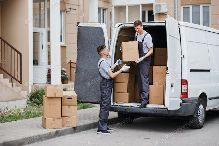Two young handsome movers wearing uniforms are unloading the van full of boxes. House move, mover