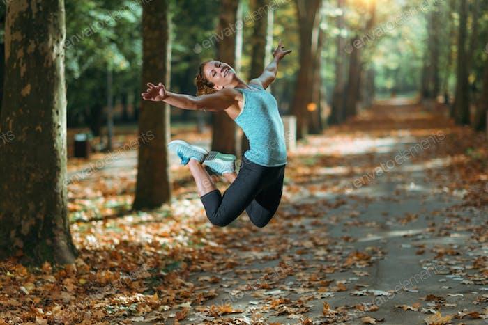 Woman Doing Star Jump Outdoors