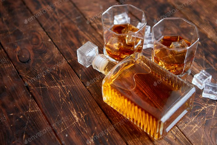 Bottle of whiskey with two glasses placed on rustic wooden table
