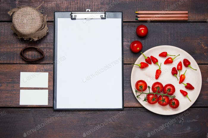 Office desk table with pencils, supplies and vegetables
