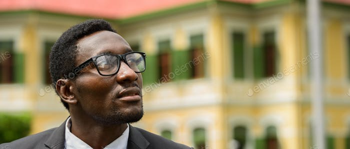 Happy young African businessman with eyeglasses thinking in the city streets outdoors