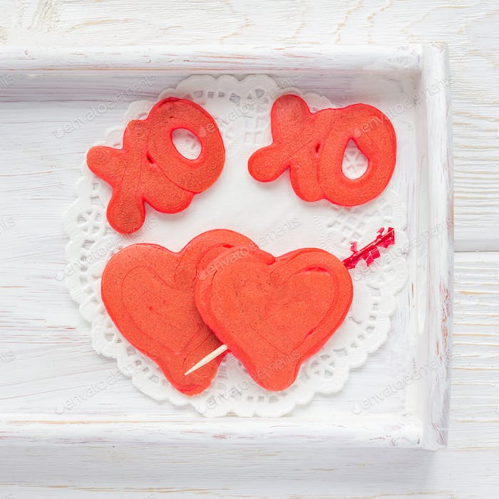 Red velvet pancakes with xo sign, hugs and kisses, and heart on wooden tray, top view, square
