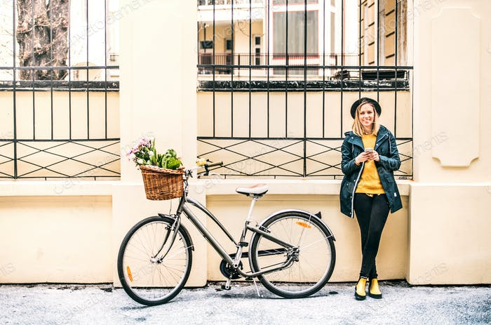Young woman with bicycle and smartphone in sunny spring town.