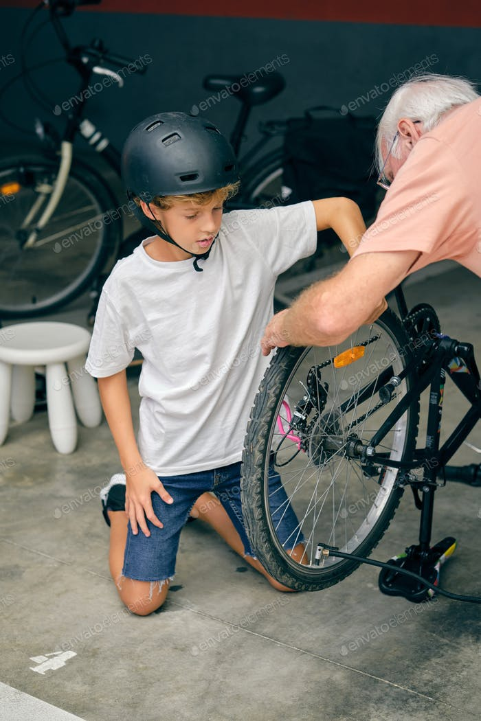 Concentrated boy inflating tire with grandfather