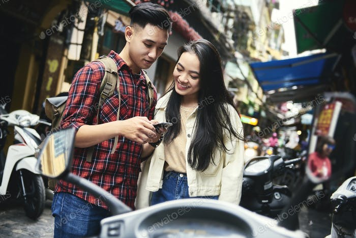 Young couple using phone on the street
