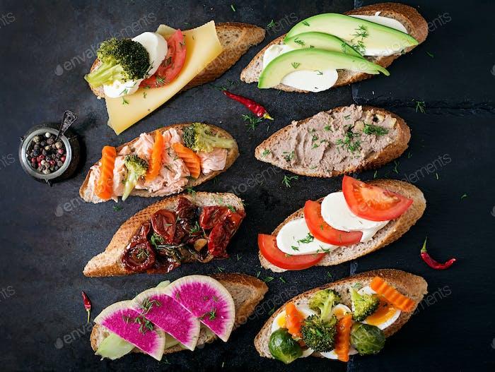Vielzahl von gesunden Sandwiches auf einem dunklen Hintergrund in einem rustikalen Stil. Ansicht von oben