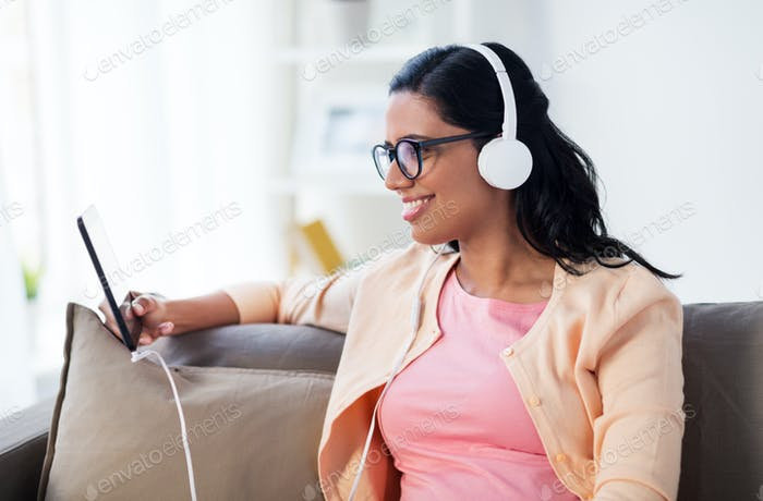 happy woman with tablet pc and headphones at home